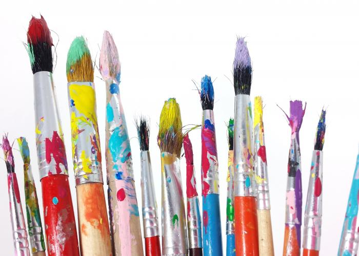 A grouping of art paintbrushes in various sizes, covered in splattered paint colours and set against a white background.