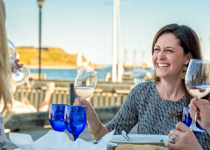 A smiling brunette woman raises a glass of white wine during a patio dinner at a restaurant on the Halifax waterfront.