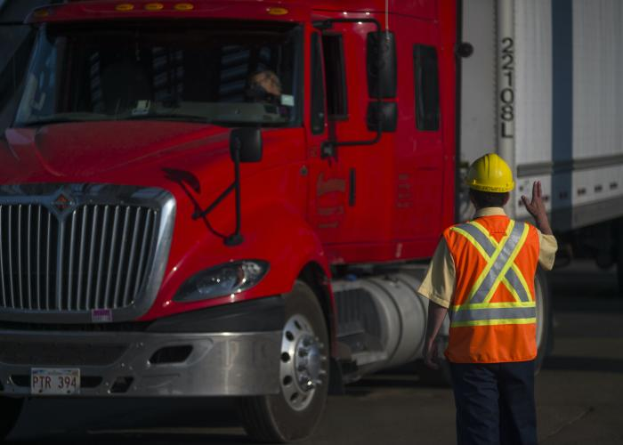 Attendant at Port-aux-basques commercial loading lot directs truck
