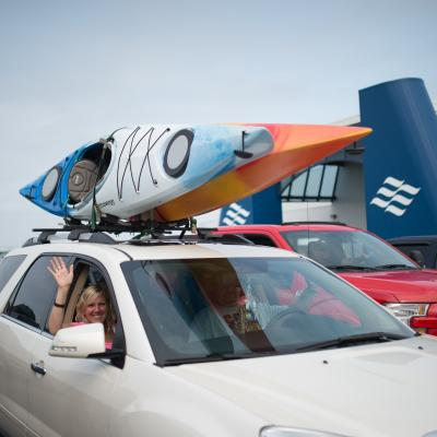 Passenger waving from car with kayaks on roof.