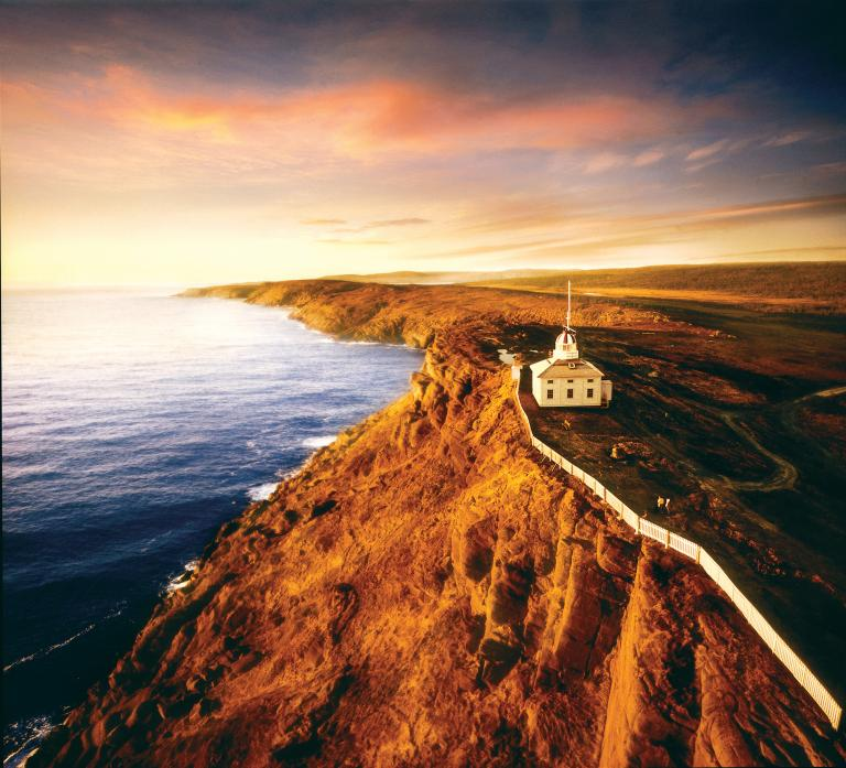 An aerial shot at sunrise shows a white picket fence along a rocky red cliff at the Cape Spear National Historic lighthouse.