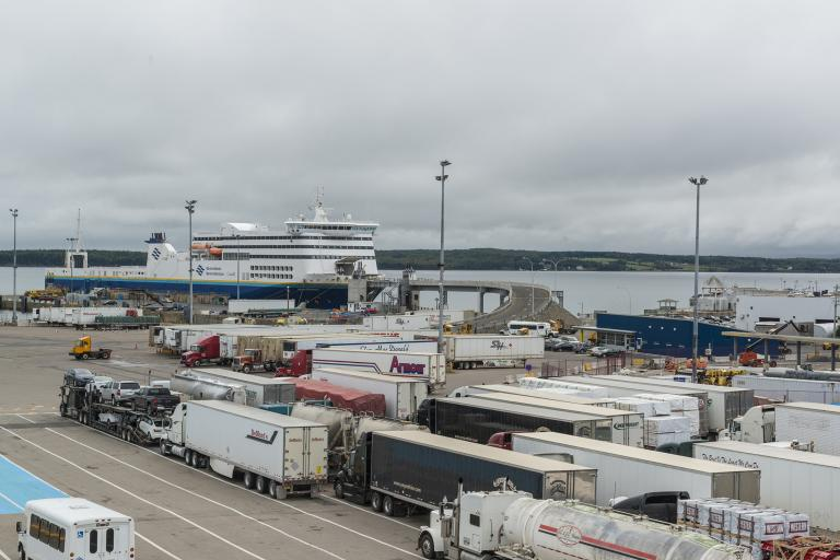 Multiple lanes of transport trucks and cars line up to board a Marine Atlantic ferry in North Sydney, Nova Scotia.