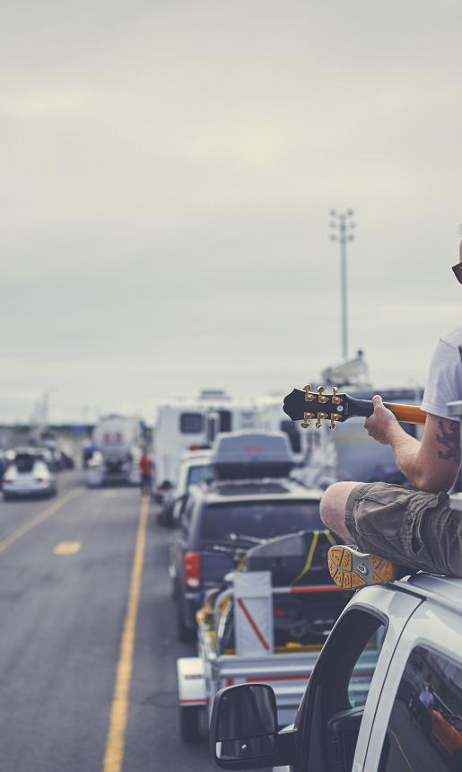 A ponytailed man in his twenties sits on top of a van and plays guitar while waiting to board a Marine Atlantic ferry.