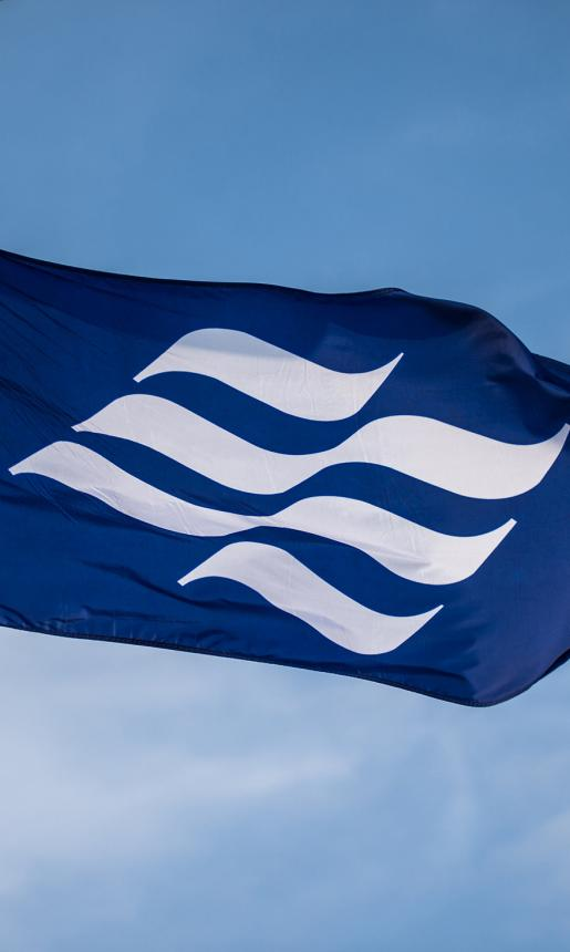 The royal blue Marine Atlantic flag with undulating white wave emblem blows in the wind onboard a ferry.