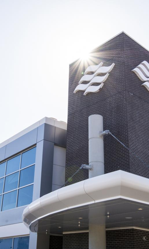 The sun shines down on the brick facade and Marine Atlantic wave logo of a modern looking office building/ferry terminal.